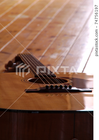 Board floor and acoustic guitar. 74756197
