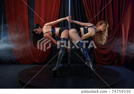 Two sexy striptease dancers on stage, pole dance 74759330