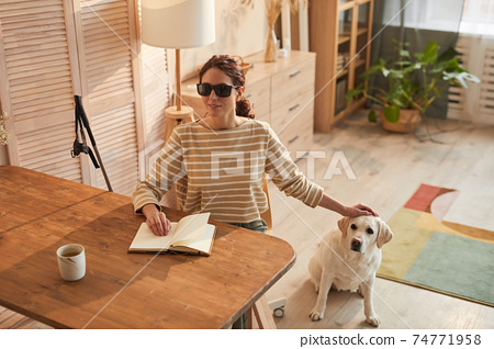 Portrait of Blind Woman at Home with Guide Dog 74771958