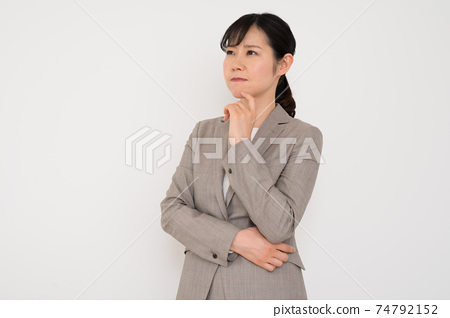 A woman in a business suit with a troubled expression 74792152
