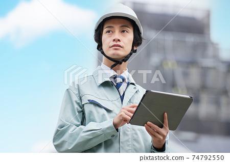 一個穿著工作服的人看著平板電腦在一個建築工地 74792550