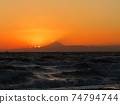 Mt. Fuji as the sun sets and floats in the sunset 74794744