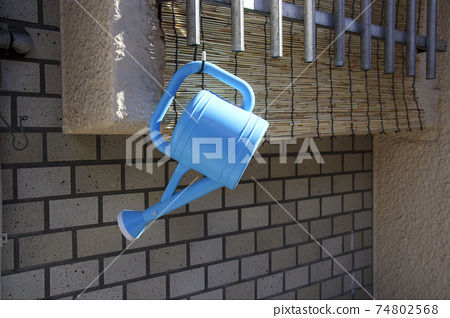 Blue watering can of plastic hanging from the window 74802568