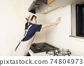 A female house cleaning worker cleaning the area around the gas stove 74804973