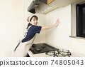 A female house cleaning worker cleaning the area around the gas stove 74805043