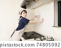 A female house cleaning worker cleaning the area around the gas stove 74805092