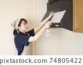 가스 레인지 후드에 베이킹 소다 시트를 붙이는 집 청소 여성 노동자 74805422