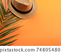 Vacation concept with straw hat and fern on orange 74805480