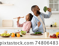 Black father and daughter singing in the kitchen together 74806483