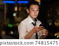 晚上在辦公室使用智能手機的商人 74815475