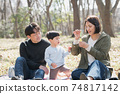 Image of a Japanese family playing with soap bubbles, a parent and child having a picnic in the park 74817142