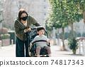 유모차로 산책하는 남자와 마스크를 붙인 어머니 코로나 재난의 육아 이미지 74817343