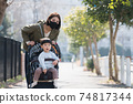行走在嬰兒小推車裡的男孩和戴著面具,電暈的母親的育兒形象 74817344