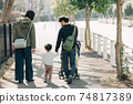 Family image of a couple raising children, parents and children walking in a residential area holding hands 74817389