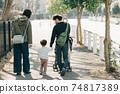 손을 잡고 주택가를 산책 부모와 자식 소년의 육아를하는 부부의 가족 이미지 74817389
