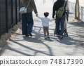 Family image of a couple raising children, parents and children walking in a residential area holding hands 74817390