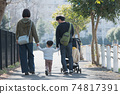 Family image of a couple raising children, parents and children walking in a residential area holding hands 74817391