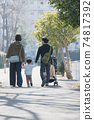 Family image of a couple raising children, parents and children walking in a residential area holding hands 74817392