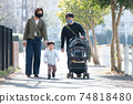 Family image of a family walking in a residential area wearing a corona-damaged child-rearing / mask 74818480