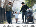 行走在居民區的家庭的家庭形象,身上戴著電暈損壞的撫養孩子的面具 74818482