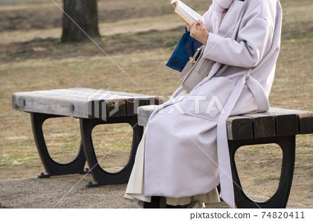 공원 의자에 앉아 독서하는 여성 74820411