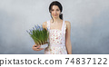 Woman Holding Bouquet of Flowers in Hands Indoors 74837122