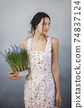 Woman Holding Bouquet of Flowers in Hands Indoors 74837124