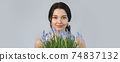 Woman Holding Bouquet of Flowers in Hands Indoors 74837132