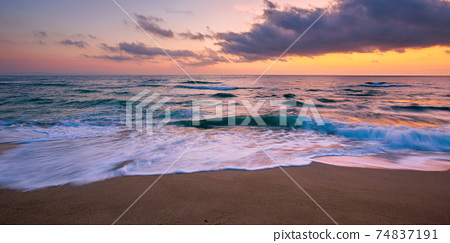 sea beach with dramatic sky at sunrise. beautiful vacation background. waves rolling on the sand in morning light 74837191