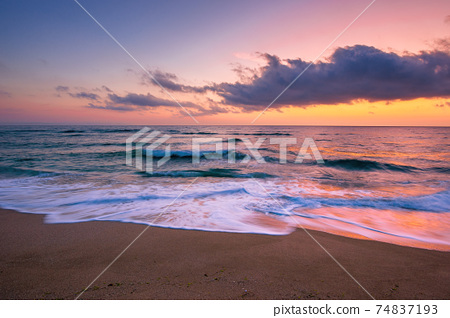 sea beach with dramatic sky at sunrise. beautiful vacation background. waves rolling on the sand in morning light 74837193