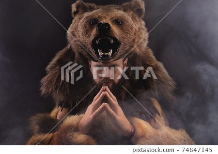 Magic fighting shaman werewolf man with a beard in a fur dress in a dark room. Cosplay on the theme of transformation of a bear into a human 74847145