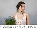 Woman Holding Bouquet of Flowers in Hands Indoors 74849532