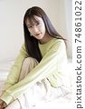 Portrait of a beautiful woman sitting on the bed 74861022