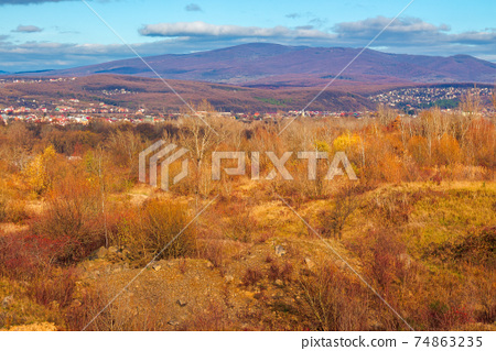 rural valley in the morning. beautiful autumn scenery in mountains. town in the distant valley. clouds on the blue forenoon sky 74863235