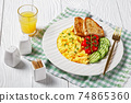 scrambled eggs with veggies and bread on a plate 74865360