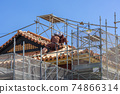 Workers working on tiled roofs 74866314