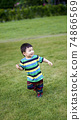little child wear casual suit playing in the park.  74866569