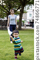 Mother and child are playing in the playground.  74866771