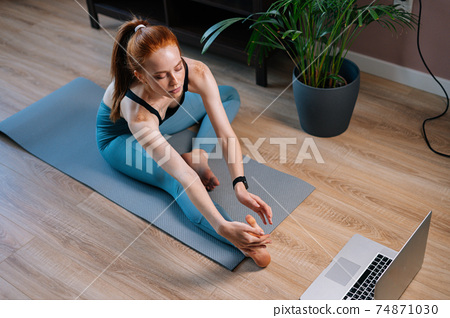 Top view of flexible redhead young woman working out, doing stretching exercise on yoga mat. 74871030