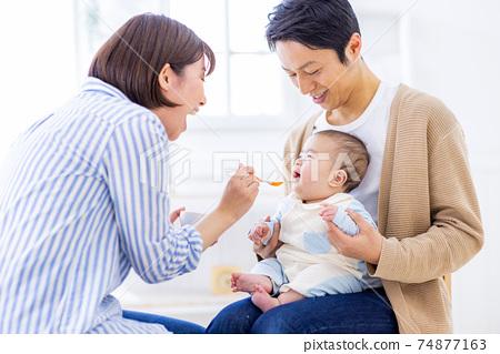 嬰兒試圖吃嬰兒食品 74877163