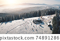 Winter snow resort at sun mountain aerial. People at nature landscape. Ski slope for active sport 74891286