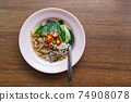 Fried Wide Rice Noodles with Pig in Gravy Sauce on the Wood Table 74908078
