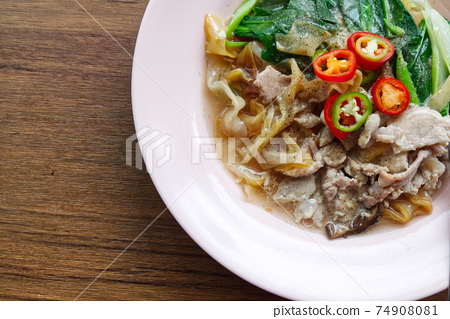 Fried Wide Rice Noodles with Pig in Gravy Sauce on the Wood Table 74908081