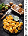 Duchess potatoes served on a black plate 74910451