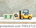 Toy forklift hold letter block Q to complete word RFQ (abbreviation of request for quotation) on wood background 74912712