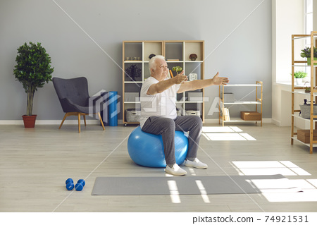 Elderly man sitting and exercising on fitness ball with arms stretched at home or in rehabilitation clinic 74921531