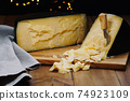 Medium hard cheese head parmesan on wooden board, with cheese parmesan knifes. 74923109