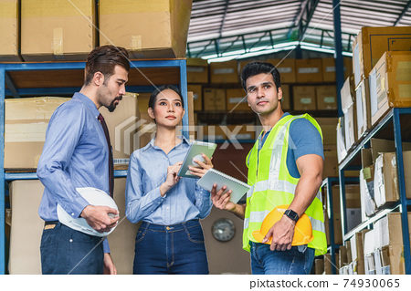 White Caucasian Manager of warehouse worker assign and discuss with Asian assistant manager woman and Indian Worker man in local factory, Partner and colleague working together concept 74930065