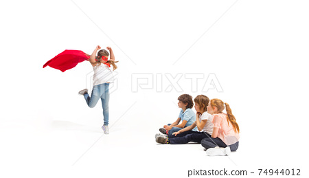 Child pretending to be a superhero with her friends sitting around 74944012
