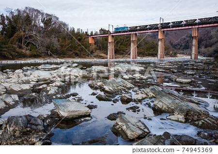흐린 날씨 속에서 강을 빠져 나온 지 치부 철도의 전기 기관차 74945369